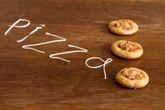 Tres mini pizzas con la salchicha y el queso en la tabla de madera Foto de archivo libre de regalías