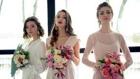 Tres modelos de las novias contra la perspectiva de una ventana grande hermosa En las manos del diseñador elegante bouquets-2 almacen de metraje de vídeo