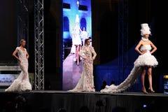 Tres modelos de moda en una etapa, blanco que lleva se visten Imagenes de archivo