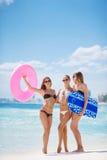 Tres modelos en una playa tropical con un círculo Imagen de archivo