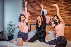 Tres modelos jovenes se divierten en cama en sitio Fingen el canto en cosas que tienen en manos Las muchachas guardan sus manos p imágenes de archivo libres de regalías