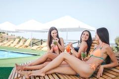 Tres modelos que se sientan y que mienten en sunbeds Se enfrían Las mujeres jovenes beben los cócteles y tienen mirada de los mod fotos de archivo