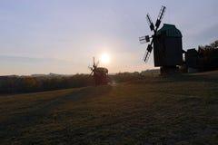 Tres molinoes de viento en una pequeña colina cerca del bosque en el backgroun Fotos de archivo