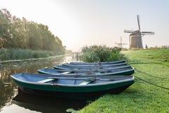 Tres molinos de viento de Molendriegang Leidschendam, Países Bajos durante una salida del sol brumosa con cinco barcos de rowing  foto de archivo