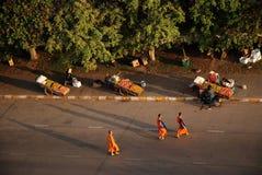 Tres monjes laosianos que cruzan una calle a finales de tarde imagen de archivo
