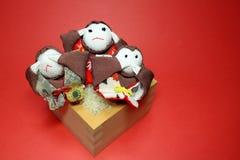 Tres monos sabios y taza de medida de madera del arroz en el rojo Foto de archivo libre de regalías