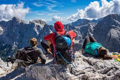 Tres montañeses que se sientan en la roca en el top de la montaña de Prisojnik fotografía de archivo libre de regalías