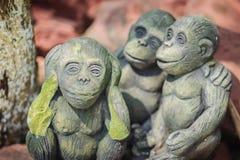 Tres muñecas del mono se moldean usando los oídos del cierre de la acción de la mano, ojos Foto de archivo
