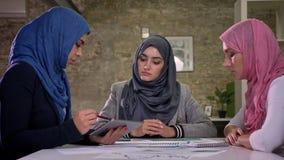 Tres muchachas árabes del hijab están sentando todos juntas en teble grande y están hablando con los pacientes sobre el trabajo,  metrajes