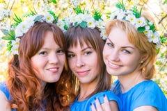 Tres muchachas 30 años con las guirnaldas en la cabeza Imágenes de archivo libres de regalías