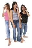Tres muchachas adolescentes con los teléfonos celulares sobre blanco Imagenes de archivo
