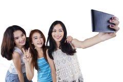 Tres muchachas alegres que toman el selfie Imagen de archivo