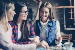 Tres muchachas alegres sonrientes que juegan al juego de mesa imágenes de archivo libres de regalías