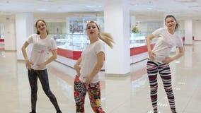 Tres muchachas atractivas bailan el twerk en un pasillo grande metrajes