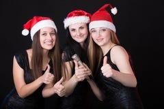 Tres muchachas atractivas de santa con la demostración del micrófono Fotografía de archivo