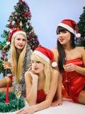 Tres muchachas atractivas que desgastan la ropa de Papá Noel Fotos de archivo