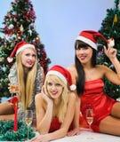 Tres muchachas atractivas que desgastan la ropa de Papá Noel Imágenes de archivo libres de regalías