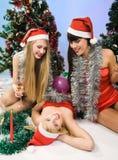 Tres muchachas atractivas que desgastan la ropa de Papá Noel Fotografía de archivo