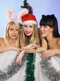 Tres muchachas atractivas que desgastan la ropa de Papá Noel Imagen de archivo libre de regalías