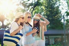 Tres muchachas atractivas que miran las fotos en su cámara las vacaciones de verano Imágenes de archivo libres de regalías