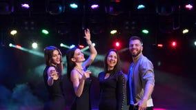 Tres muchachas atractivas y una danza del individuo en un club nocturno almacen de video
