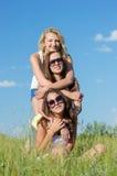 Tres muchachas bonitas felices que abrazan contra el cielo azul Foto de archivo libre de regalías