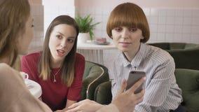 Tres muchachas caucásicas jovenes se están sentando en un café, amigos, compañía, chismes, diálogo, discusión Novias en almacen de metraje de vídeo