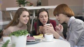 Tres muchachas caucásicas jovenes se están sentando en un café, riendo, sonriendo, amigos, compañía, chismes, diálogo, discusión almacen de metraje de vídeo