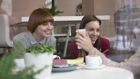 Tres muchachas caucásicas jovenes se están sentando en un café, riendo, sonriendo, amigos, compañía, chismes, diálogo, discusión almacen de video