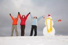 Tres muchachas con el muñeco de nieve Imágenes de archivo libres de regalías