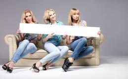 Tres muchachas con el tablero vacío Imagen de archivo