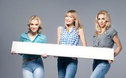 Tres muchachas con el tablero vacío fotografía de archivo