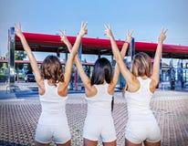 Tres muchachas con la muestra de la victoria Foto de archivo
