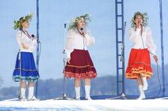 Tres muchachas con las guirnaldas cantan en la trinidad Foto de archivo libre de regalías
