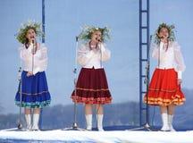 Tres muchachas con las guirnaldas cantan en la trinidad Imagen de archivo