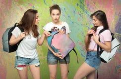 Tres muchachas con las mochilas en el fondo del color Fotografía de archivo