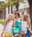 Tres muchachas con los panieres y van a hacer compras Foto de archivo libre de regalías