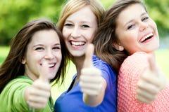 Tres muchachas con los pulgares para arriba Fotos de archivo libres de regalías
