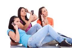 Tres muchachas con los teléfonos Fotografía de archivo