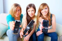 Tres muchachas con los teléfonos móviles Fotografía de archivo