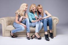 Tres muchachas con smartphone imagenes de archivo