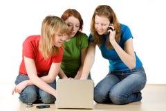 Tres muchachas con una computadora portátil Foto de archivo