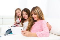 Tres muchachas de los amigos de la hermana del niño que juegan así como la PC de la tableta fotos de archivo