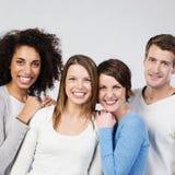Tres muchachas de risa con un amigo masculino joven Imagenes de archivo