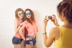Tres muchachas del inconformista del estilo de la calle que toman imágenes Imagenes de archivo