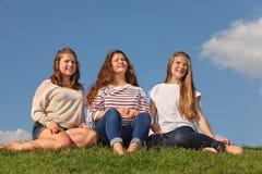 Tres muchachas descalzas se sientan y miran en distancia Imagen de archivo