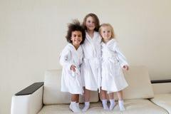 Tres muchachas divertidas en las capas blancas imagen de archivo libre de regalías