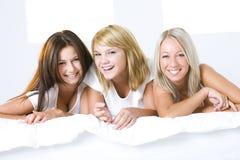 Tres muchachas en cama Fotos de archivo