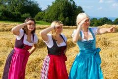 Tres muchachas en dirndl Imagen de archivo