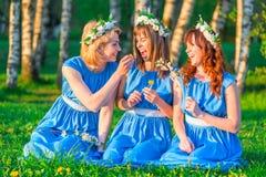 Tres muchachas en el césped en igualmente visten imagen de archivo